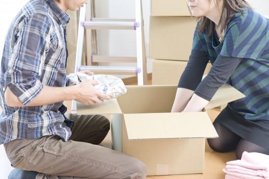 引っ越しの梱包作業をするカップル